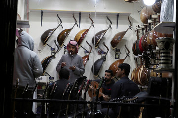 Saudi youths are seen inside a musical instruments shop at the Hilla market, in Riyadh