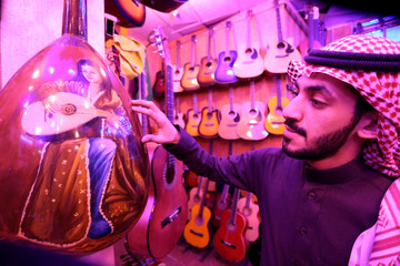 A Saudi musician looks at the design of the oud instruments in a musical instruments shop at the Hilla market, in Riyadh