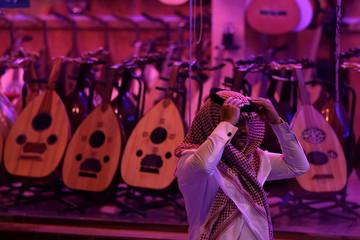 A Saudi man walks past a musical instruments shop at the Hilla market, in Riyadh