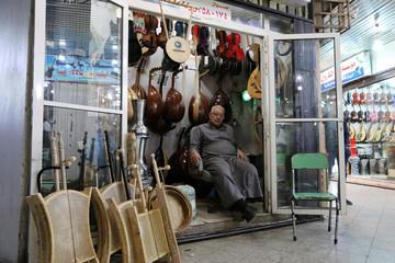 A man sits inside a musical instruments shop at the Hilla market, in Riyadh