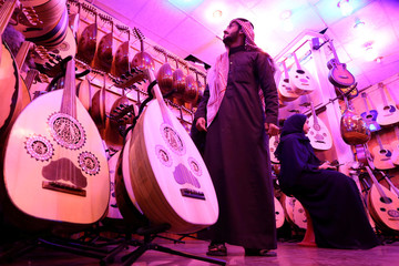 A Saudi musician looks at the oud instruments in a musical instruments shop at the Hilla market, in Riyadh