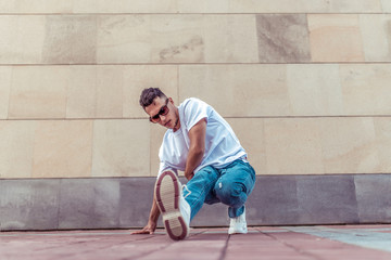 Male dancer young guy, in summer in the city, dancing street dances, modern youth style. Fashion and fitness sport. T-shirt glasses and jeans sneakers. Free space for copy text.