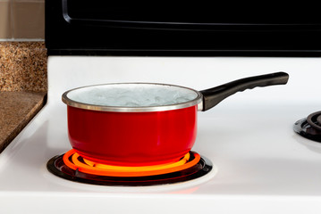 Red Pan With Boiling Water On Top of Stove