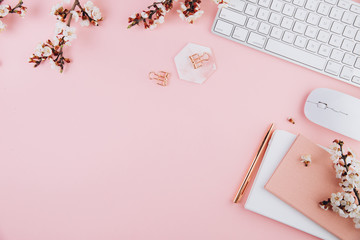 Spring flat lay top view home office workspace - modern keyboard and notebook with cherry blossom branches on a pink desk background