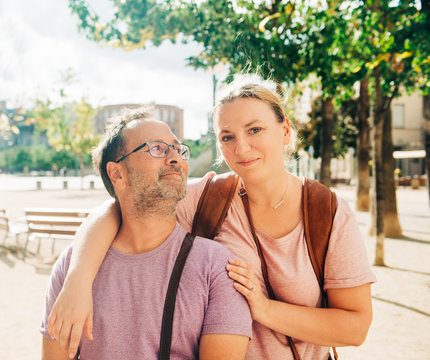 Outdoor portrait of happy middle age couple in sunlight