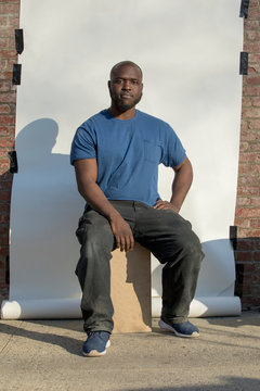 african american male construction worker in plain t-shirt millennial on white wall