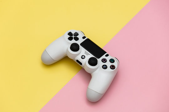 Wroclaw, Poland - 25 January 2020: Play Station 4 gamepad on yellow and pink background.