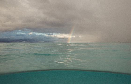 rainbow on a cloudy day over tropical lagoon