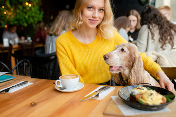 Young caucasian cheerful blonde girl sitting and hugging together with her lovely cocker spaniel dog in caffe at the table with lunch meal and cappuccino.