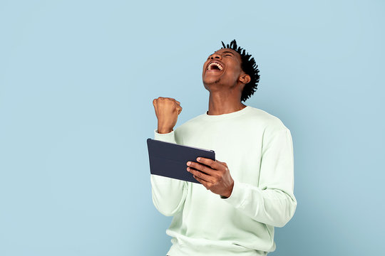 Happy african man holding tablet.