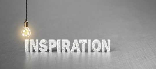 the word INSPIRATION and a light bulb on brushed aluminum background