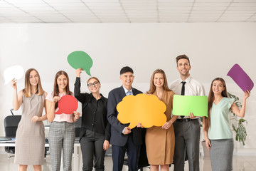 Group of business people with blank speech bubbles in office
