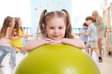 Photo sur Plexiglas Ecole de Danse Children in the gym. Preschool kid girl with fitball in physical education lesson.