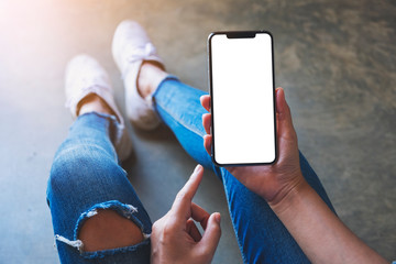 Fototapeta Mockup image of a woman holding black mobile phone with blank white screen while sitting on the floor obraz