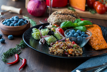Close up view of a Mediterranean diet cuisine with foods including salmon, seven grain and greek salad and blueberries.