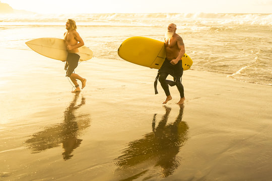 Friends going to surf on the beach at sunset. Father and son having fun doing extreme sport. Main focus on yellow surf board  - Image