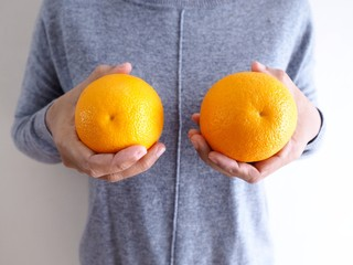 Bright yellow oranges in hands of Asian woman, Chest problems and size of breast for female. Health and Beauty Concept and breast surgery and cancer.