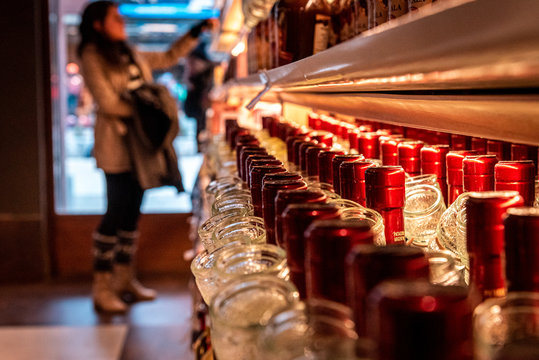 Perspective view of a bokeh of a woman shopping for wine or other alcohol in a liquor store standing in front of shelves full of bottles.