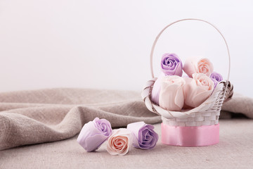 Pastel roses of violet and beige color in a white basket on a linen tablecloth.