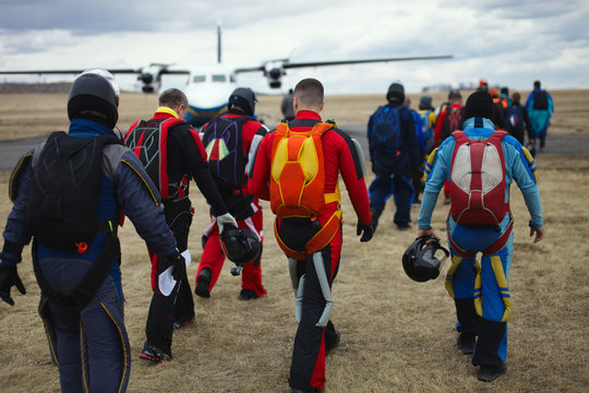 Team of skydivers with parachutes is walking to the plane before take-off, rear view, close-up.