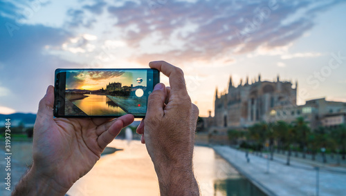 Wall mural Men using her smartphone for take a photo in Palma de Mallorca islands at sunset. In background Cathedral La Seu