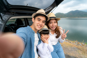 Portrait of Asian family sitting in car with father, mother and daughter selfie with lake and mountain view by smrtphone while vacation together in holiday. Happy family time.