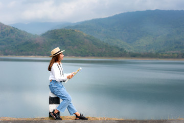 Aluminium Prints Dark grey Young beautiful Asian woman traveler with digital camera and map in hands looking and happy to see landscape view sits on a lake with beautiful mountain view in Thailand. Solo woman travel.