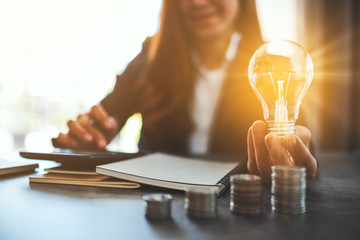 Businesswoman holding a lightbulb with coins stack on table, saving energy and money concept