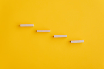 Four blank wooden pegs placed in a stairway like structure Fotomurales