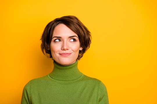 Closeup photo of funny short hairdo lady charming smiling good mood looking side empty space sly eyes wear casual green warm turtleneck isolated yellow color background