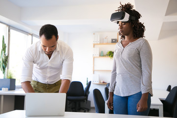 Two programmers setting VR headset. Focused workers testing new device. Technology concept