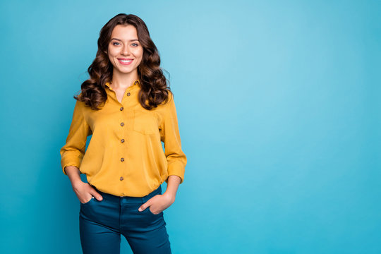 Photo of amazing curly business lady hold hands in pockets toothy beaming smiling best chief worker wear yellow shirt trousers isolated blue color background