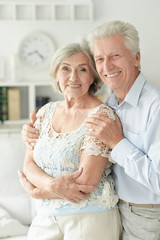 Portrait of cheerful senior couple embracing at home