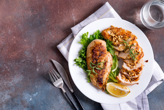 Grilled chicken breast pieces and whole and lemon slice with salad on dark stone background . Paleo diet.
