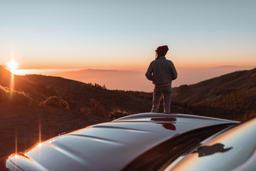Landscape view on the roadside above the clouds with woman enjoying beautiful sunset while traveling on the convertible sports car Wall mural