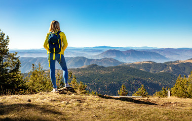 Rear view of female hiker with backpack standing on top of the mountain enjoying the view during the day.