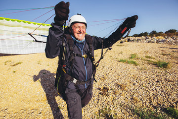 Active senior paraglider on the ground prepairs to fly.