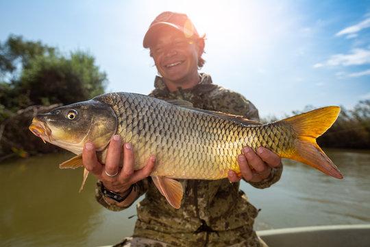 Happy angler holds big carp fish (Cyprinus carpio) and smiles. Astrakhan region, Russia