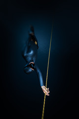 Wall Mural - Woman freediver descends along the rope into the depth. Tilt shift effect applied