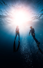 Wall Mural - Two freedivers ascend from the depth surrounded by bubbles
