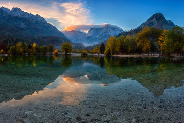 Jasna lake in Triglav national park at sunrise, Kranjska Gora, Slovenia. Amazing autumn landscape with Alps mountains, trees, blue sky with clouds and reflection in water, famous tourist attraction Fototapete