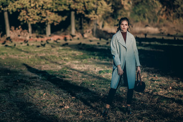 Young fashionable beautiful girl in a long gray coat, black jeans and with a dark red bag. Portrait shooting of a stylish girl. Facial shooting, street style and fashion. Professional model.
