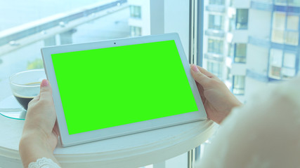 This stock photo features a woman holding her tablet with a green screen, sitting on the balcony of an apartment block with a morning coffee.