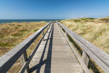Wooden footpath through the dunes leading towards the ocean on the island of Sylt in Northern Germany