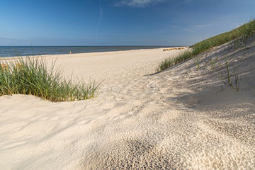 Looking onto a beautiful beach through the dunes and beach grass on the island of Sylt in Northern Germany