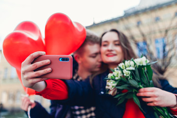 Valentines day. Couple in love taking selfie using smartphone with bouquet of flowers on date in city. Womens day