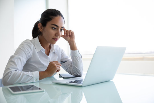 Concentrated young businesswoman using laptop in office. Focused young businesswoman sitting at desk and using laptop computer in modern office. Business and technology concept