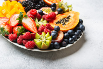 Wall Mural - Delicious fruit platter pomegranate papaya oranges grapes berries on plate on white, selective focus