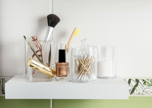 Make up products organizing in bathroom concept. Beauty products in organizer container box on tidy way on minimalist shelf. Cotton pads stacked, Q-tips and make up brushes.