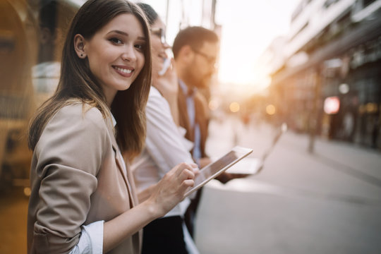 Beautiful young business woman using her tablet on her way from work.